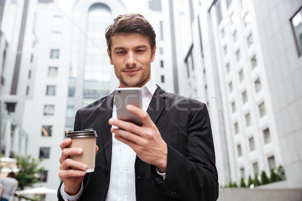 бизнесмен сотового телефона питьевой кофе город молодые Сток-фото © deandrobot
