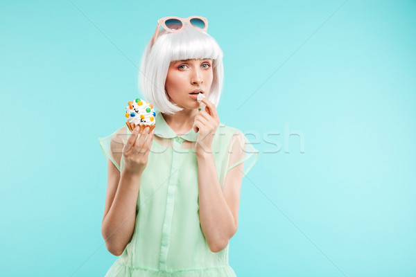 Beautiful young woman in blonde wig standing and eating cupcake Stock photo © deandrobot