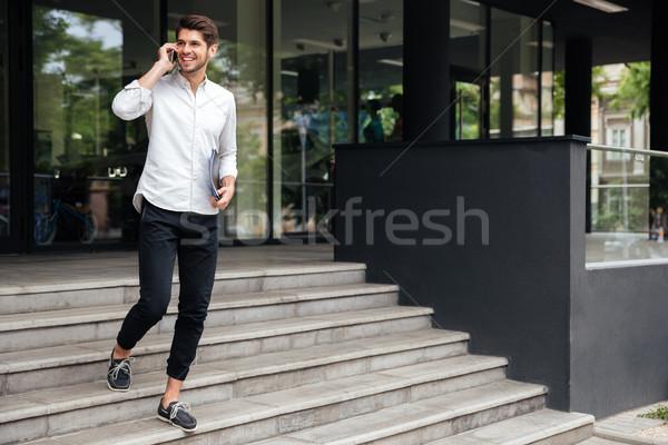 Cartelle piedi parlando cellulare esterna felice Foto d'archivio © deandrobot