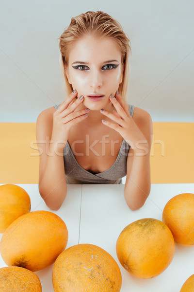 Stylish young woman with yellow melons sitting at the table Stock photo © deandrobot