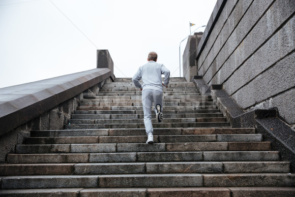 Back view of runner running on stairs Stock photo © deandrobot