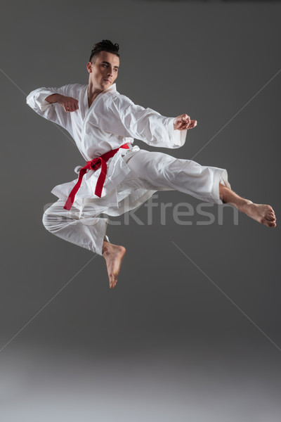 Attractive young sportsman dressed in kimono practice in karate Stock photo © deandrobot