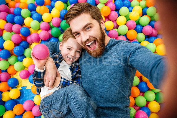 Dad and son talking selfie at pool with colorful balls Stock photo © deandrobot