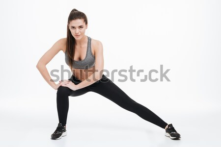 Full length portrait of a happy sporty woman stretching leg Stock photo © deandrobot