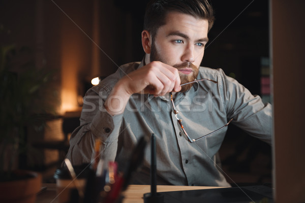 Young attractive web designer working late at night Stock photo © deandrobot