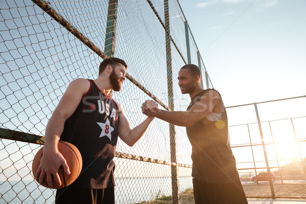 Two young basketball players greeting each other before match Stock photo © deandrobot