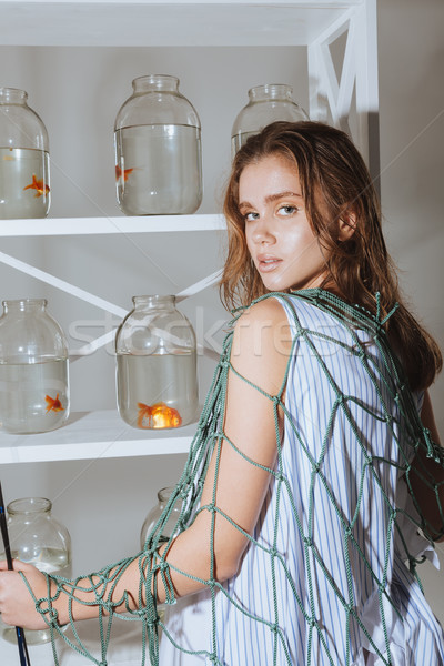 Woman in fishing net standing near closet with gold fishes Stock photo © deandrobot