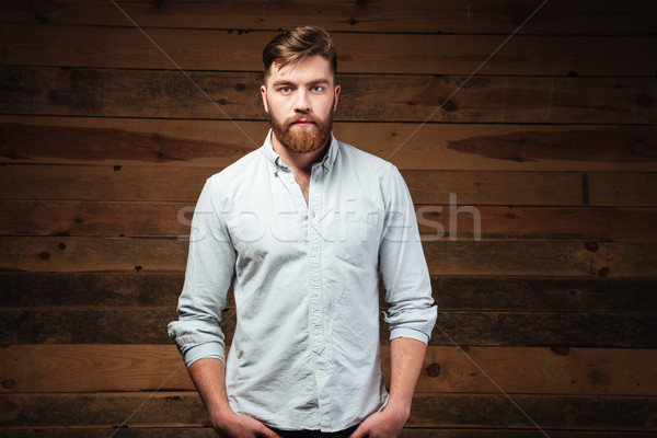 Young bearded man standing and looking at camera Stock photo © deandrobot