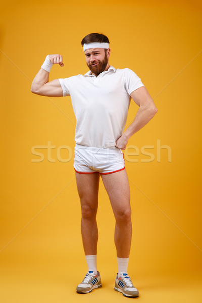 Vertical image of funny sportsman showing bicep Stock photo © deandrobot