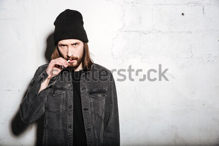 Hipster in snap back holding his cheeks Stock photo © deandrobot