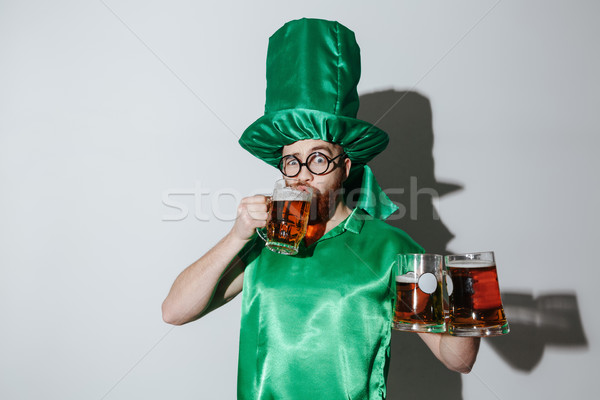 Man in st.patriks costume drinking beer and holding cups Stock photo © deandrobot