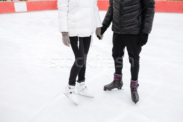 Cropped image of young loving couple skating at ice rink Stock photo © deandrobot