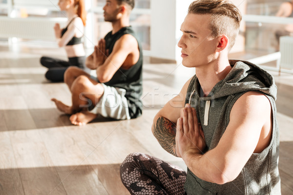 Man siting in lotus pose and doing yoga at studio Stock photo © deandrobot