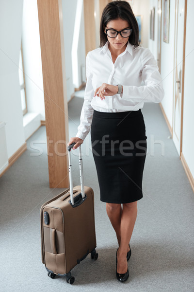 Woman in skirt walking with suitcase along hotel lobby a Stock photo © deandrobot