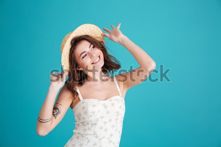 Happy young lady standing and pointing to her tattoo. Stock photo © deandrobot