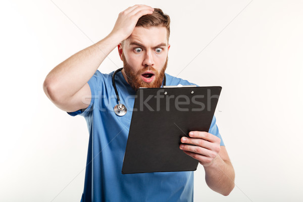 Surprised young doctor holding a clipboard and scratching his head Stock photo © deandrobot