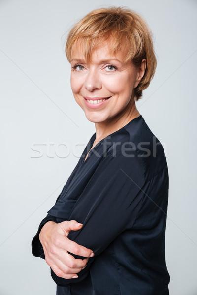Vertical image of elderly woman standing sideways Stock photo © deandrobot