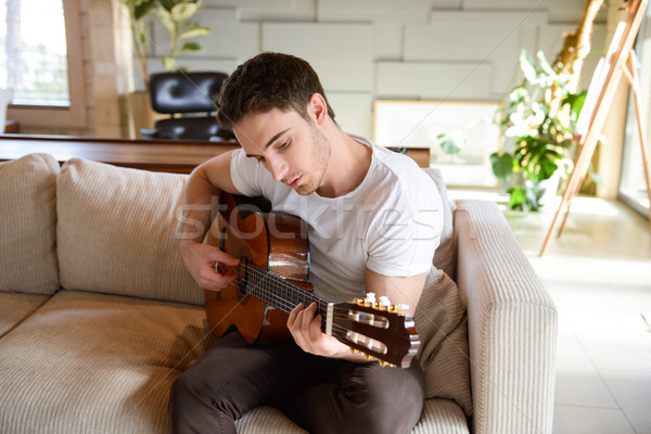 Feltalálás új dallam férfi kanapé játszik Stock fotó © deandrobot