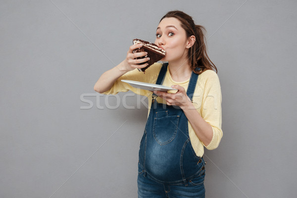 Stock photo: Portrait of a hungry pregnant woman eating sweet chocolate cake
