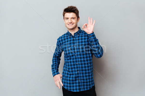 Happy man standing over grey wall and showing okay gesture Stock photo © deandrobot