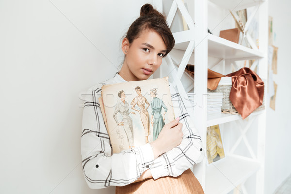Young woman fashion designer holding sketchbook Stock photo © deandrobot