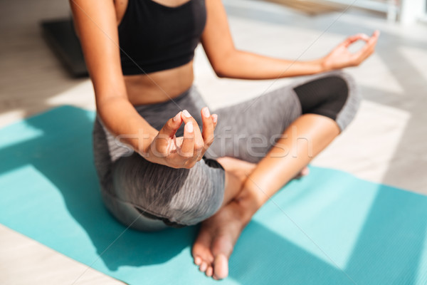 Cropped shot of fitness woman sitting in lotus pose Stock photo © deandrobot