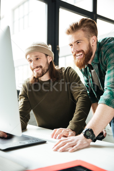 Happy men colleagues in office using computer. Looking aside. Stock photo © deandrobot