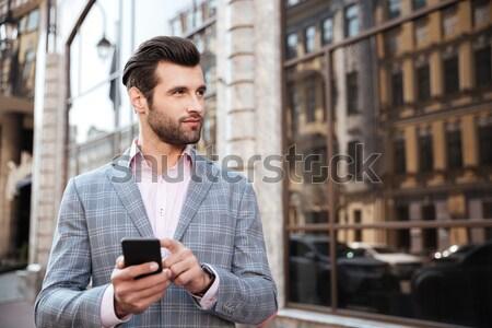 Szczęśliwy przystojny mężczyzna kurtka patrząc telefonu komórkowego portret Zdjęcia stock © deandrobot