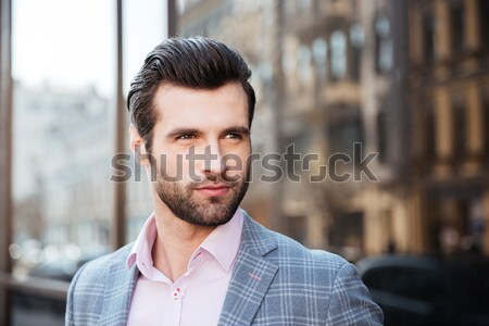 Stock photo: Portrait of a young handsome man in jacket holding laptop