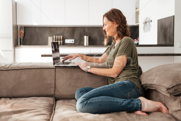Side view of Smiling casual woman sitting on sofa Stock photo © deandrobot