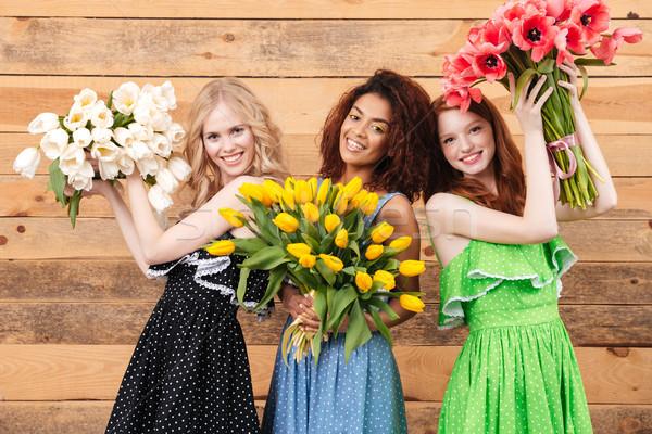 Drie tevreden vrouwen bloemen jurken Stockfoto © deandrobot