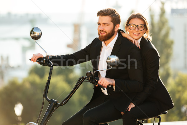 Side view of smiling couple in suits rides on motorbike Stock photo © deandrobot