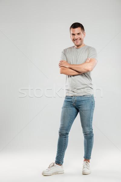 Boldog fiatalember keresztbe tett kar néz kamera szürke Stock fotó © deandrobot