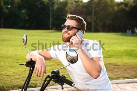 Smiling bearded man in sunglasses sitting on modern motorbike Stock photo © deandrobot