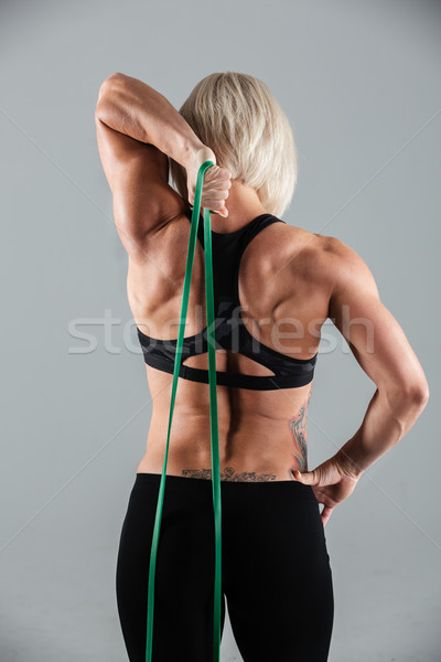 Stock photo: Back view of muscular fitness girl stretching with elastic rubbe