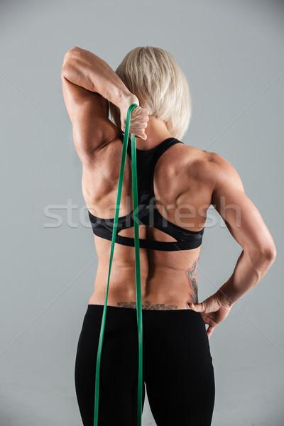 Hátulnézet izmos fitnessz lány nyújtás rugalmas Stock fotó © deandrobot