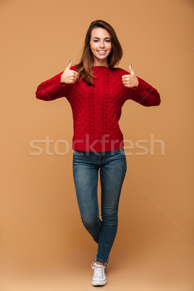 Full length portrait of smiling brunette woman in red knitted sw Stock photo © deandrobot