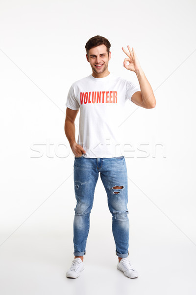 Full length portrait of a young man in volunteer t-shirt Stock photo © deandrobot