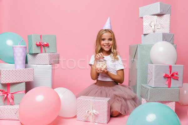 Portrait of a smiling pretty girl in a birthday hat Stock photo © deandrobot