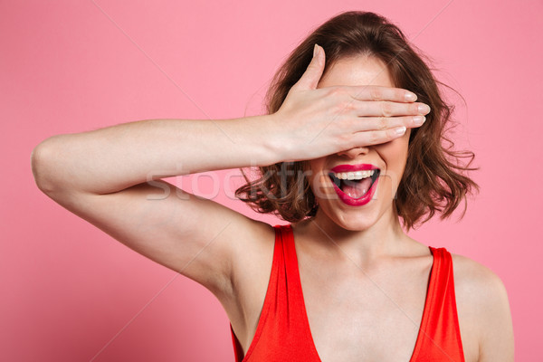 Close-up portrait of charming smiling brunette woman hiding eyes Stock photo © deandrobot