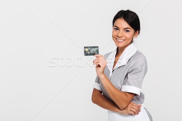 Cheerful brunette maid in uniform holding credit card and lookin Stock photo © deandrobot
