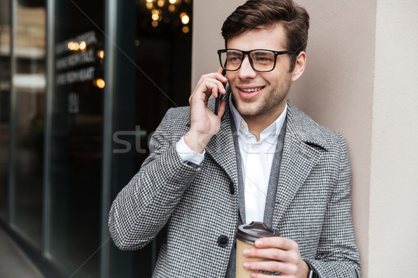 Smiling business man in eyeglasses and coat talking by smartphone Stock photo © deandrobot