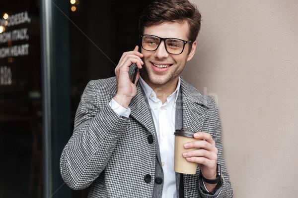 Zadowolony człowiek biznesu okulary płaszcz mówić smartphone Zdjęcia stock © deandrobot