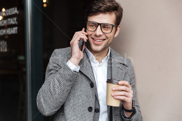 Tevreden zakenman bril jas praten smartphone Stockfoto © deandrobot