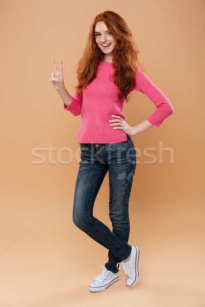 Full length portrait of a cheery smiling redhead girl Stock photo © deandrobot