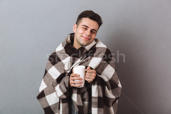 Cheerful man in warm plaid holding hot tea. Looking camera. Stock photo © deandrobot