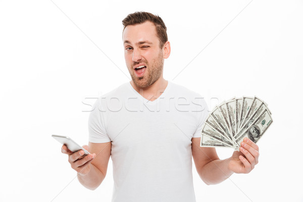 Handsome young man using mobile phone holding money. Stock photo © deandrobot