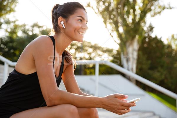 Portré boldog fitnessz lány fülhallgató ül Stock fotó © deandrobot