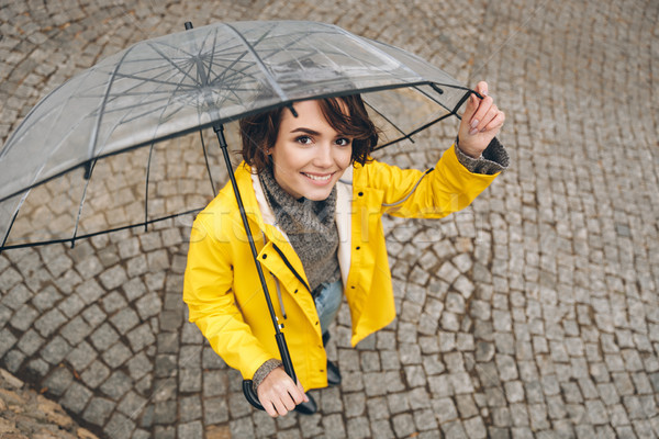 Shot from above of wonderful woman in yellow raincoat being happ Stock photo © deandrobot