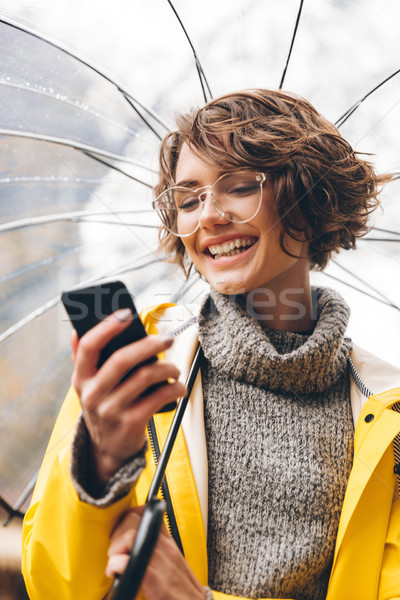 Young woman dressed in raincoat walking outdoors Stock photo © deandrobot